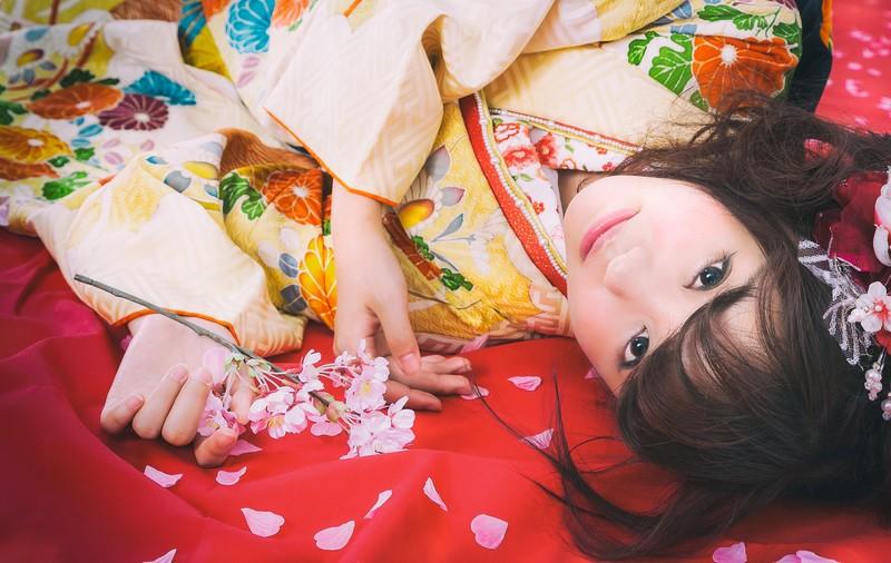 年明け・年賀イメージ・桜散る毛氈に寝転がる振袖美女